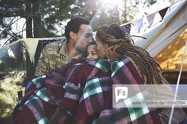 Happy  affectionate parents kissing son  relaxing at campsite