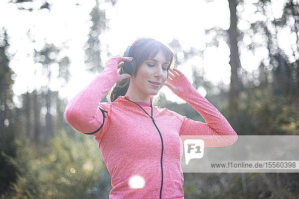 Female runner with headphones in woods