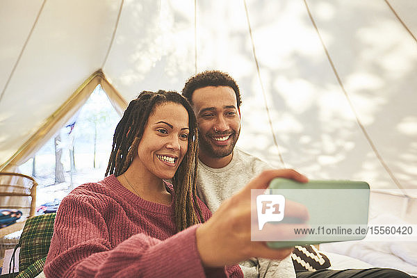 Happy couple taking selfie in camping yurt