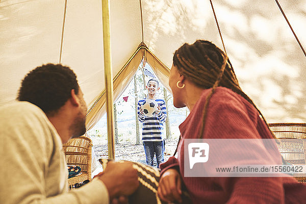 Couple watching son with soccer ball at camping yurt doorway