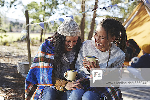 Happy  carefree lesbian couple laughing  drinking coffee at campsite