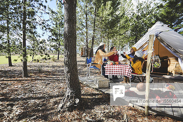 Lesbian couple and kids toasting mugs at sunny campsite table in woods