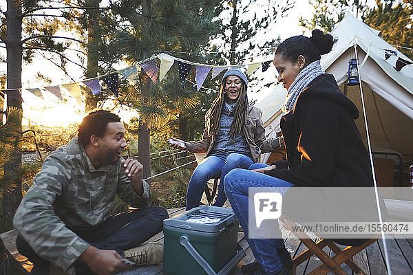 Happy friends playing cards at campsite in woods
