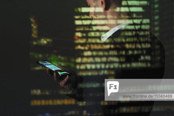 Doppelbelichtung Geschäftsmann mit Smartphone gegen Hochhaus bei Nacht