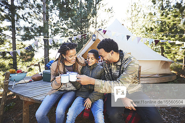 Glückliche Familie trinkt Kaffee und heiße Schokolade auf einem Campingplatz im Wald
