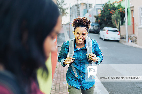 Laughing  happy young woman with backpack on sidewalk