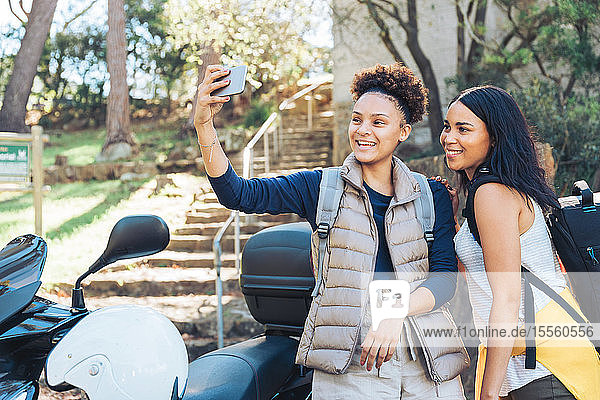 Happy young women friends taking selfie with camera phone at motor scooter