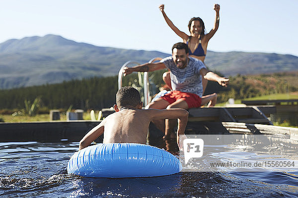 Playful family swimming in sunny  summer swimming pool