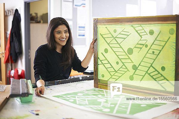 Smiling female art student screen printing in art studio