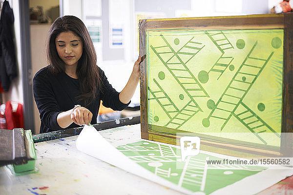 Female artist screen printing in studio