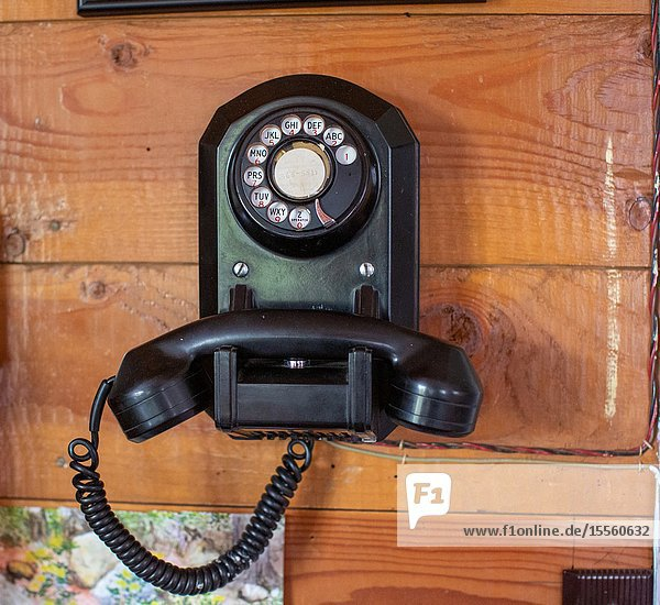 A rotary dial telephone is still in use.