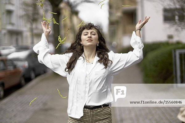 Young woman tossing inflorescences in the air  Berlin  Germany.