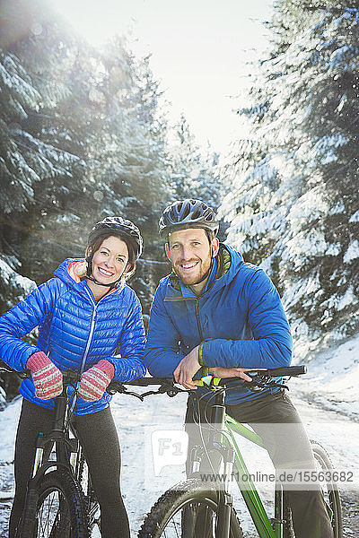 Portrait couple mountain biking in snow