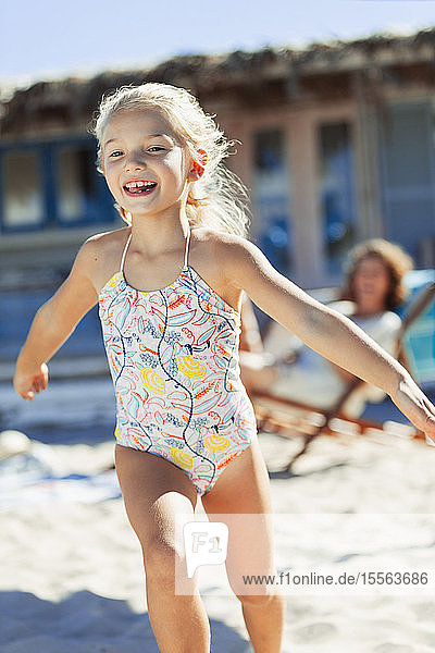 Carefree girl in bathing suit running on sunny beach