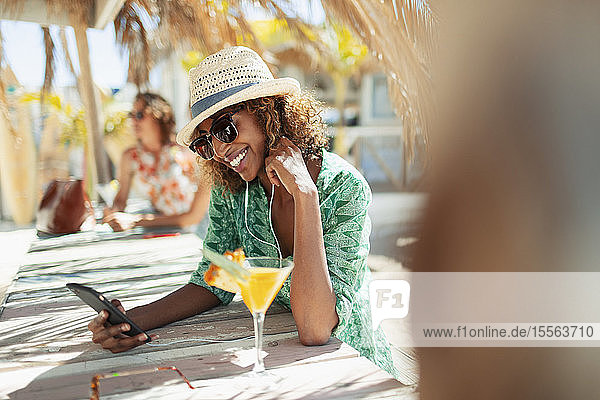 Happy young woman with smart phone drinking cocktail at sunny beach bar