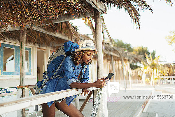 Young female backpacker using smart phone on beach hut patio