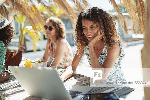 Young woman using laptop at sunny beach bar