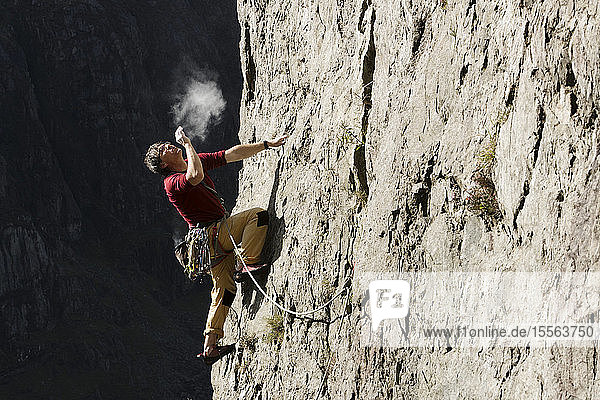 Male rock climber scaling rock face,  looking up and blowing chalk on hands