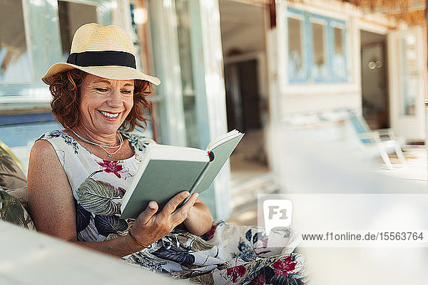 Happy woman reading book on beach hut patio