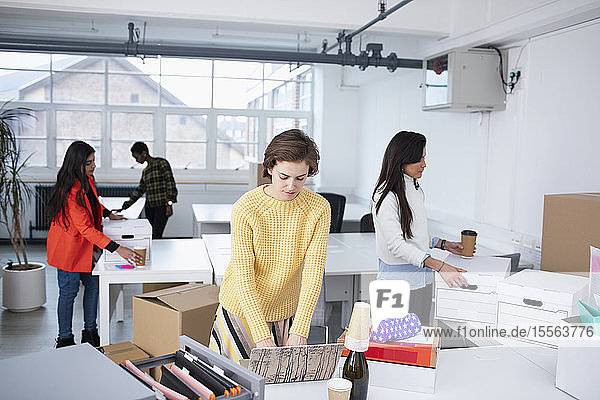 Businesswomen unpacking and working in new office