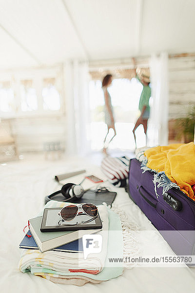 Suitcase  books  beach towels and sunglasses on beach hut bed
