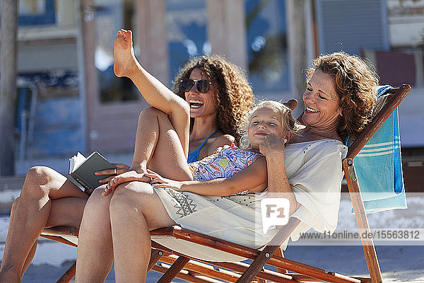Playful  happy multi-generation women relaxing on sunny beach