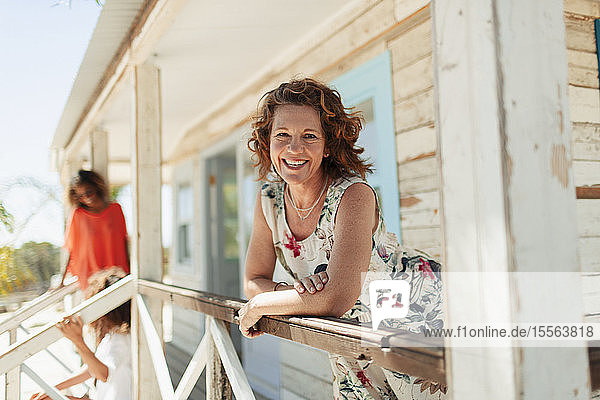 Portrait smiling  confident woman on sunny beach hut patio