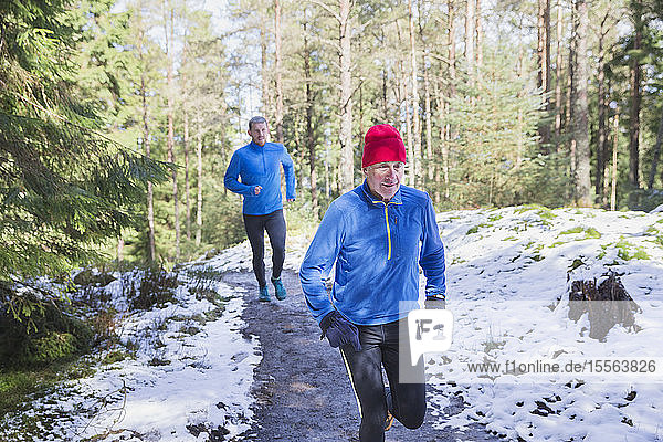 Father and son jogging in snowy woods