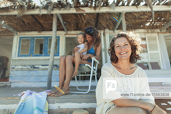 Portrait happy multi-generation women on beach hut patio