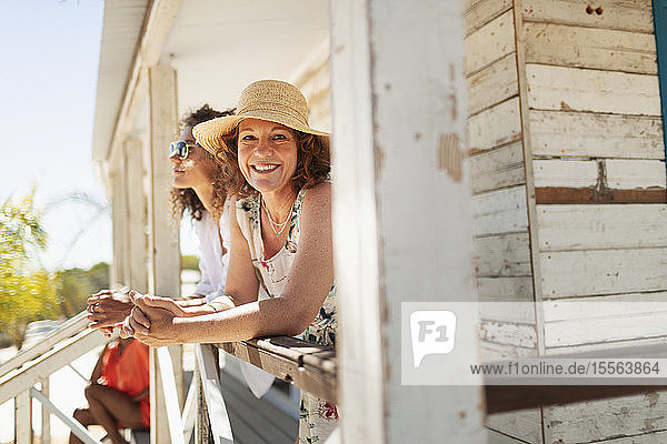 Portrait happy woman on sunny beach hut patio