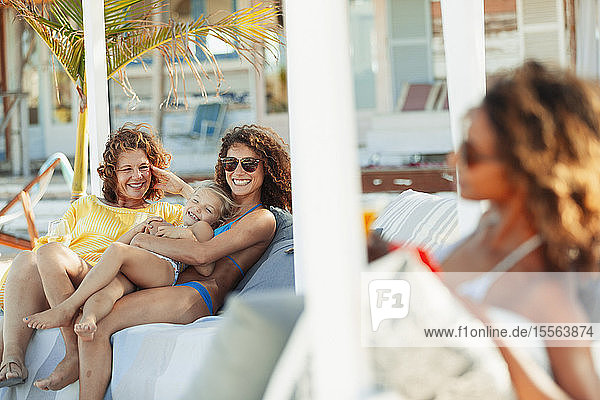 Happy multi-generation women relaxing on beach patio