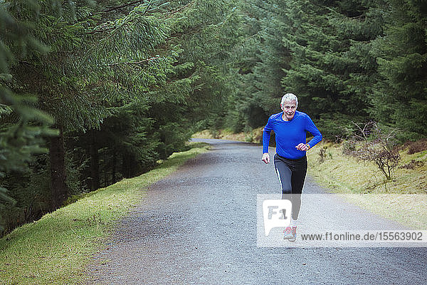 Senior man jogging in woods