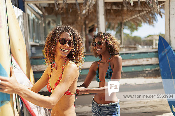 Happy young women with surfboards on sunny beach