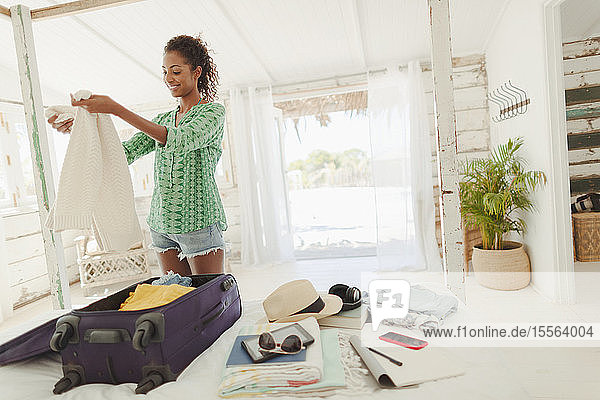 Young woman unpacking suitcase on beach hut bed
