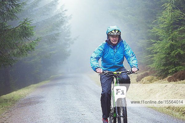 Senior man mountain biking in woods