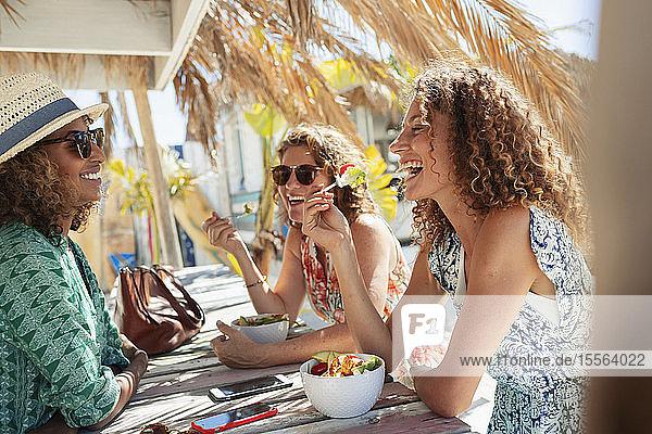 Happy women friends eating salad at sunny beach bar