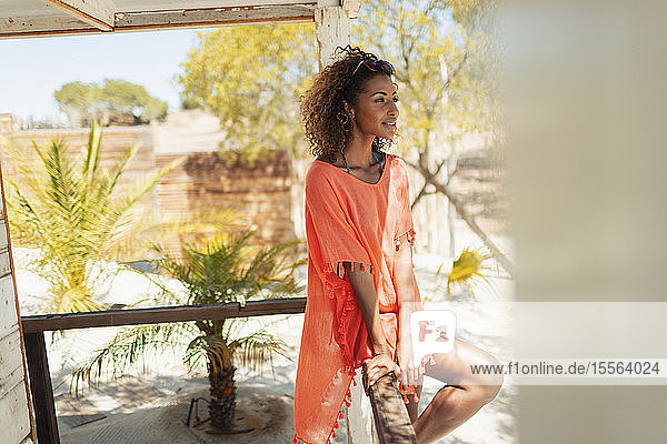 Serene young woman relaxing on sunny beach hut patio