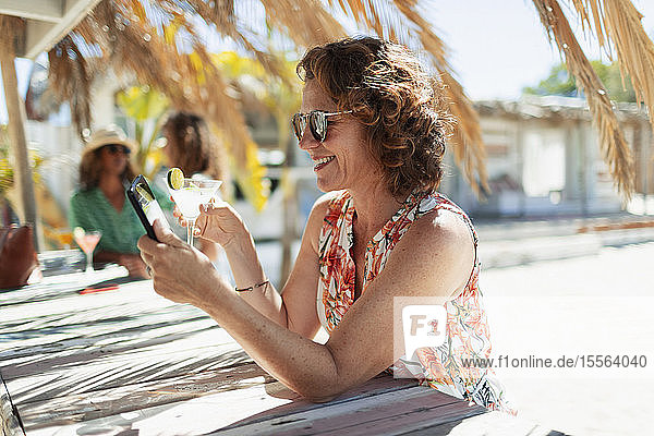 Carefree woman drinking cocktail and using smart phone at sunny beach bar
