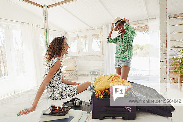 Young women friends unpacking suitcase in beach hut bedroom