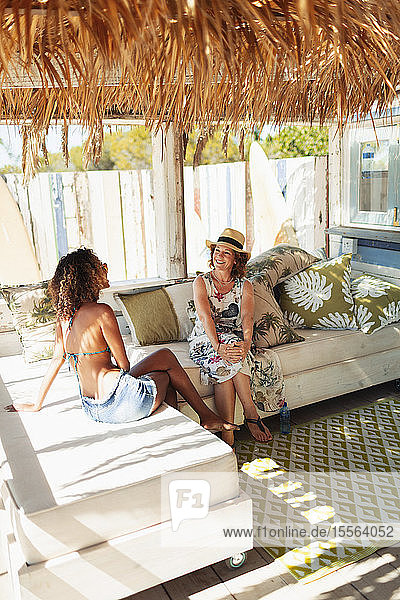 Mother and adult daughter talking and relaxing on beach hut patio