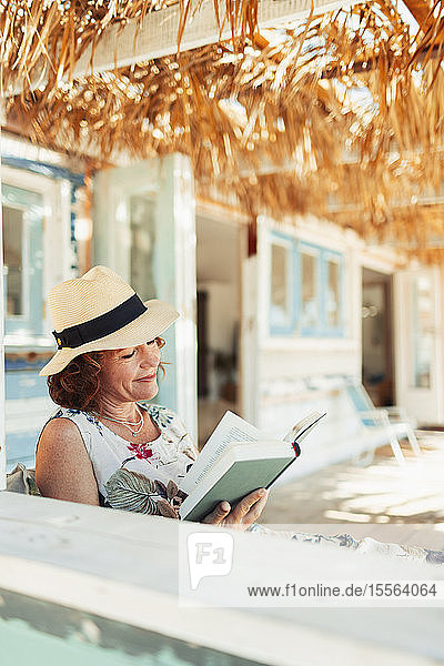 Woman reading book on beach hut patio