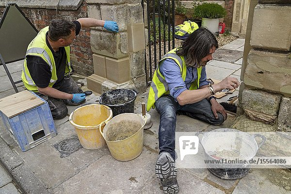 Salisbury  Wiltshire  England  UK. Stone masons working on a gateway  replacing stone and repairing mortar.