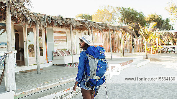 Young female backpacker arriving at beach hut