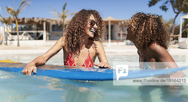 Happy sisters with surfboard in sunny ocean