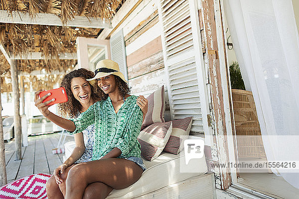 Happy young women friends taking selfie with camera phone on beach hut patio
