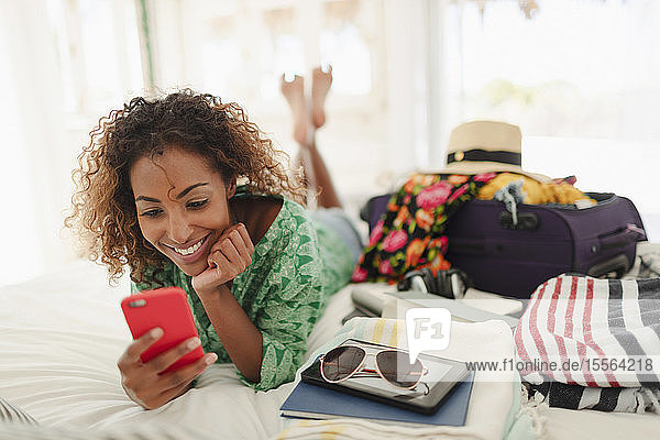 Young woman with smart phone unpacking suitcase on bed