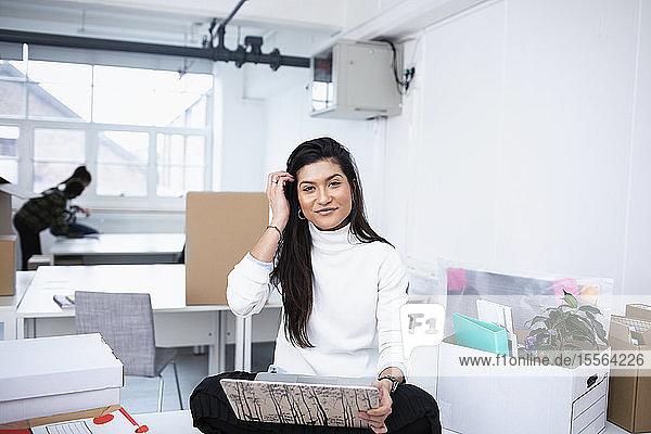 Portrait confident businesswoman using laptop in new office