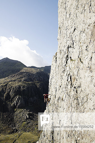 Male rock climber scaling large rock face