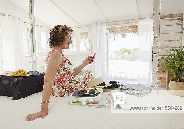 Woman with smart phone unpacking suitcase on beach hut bed