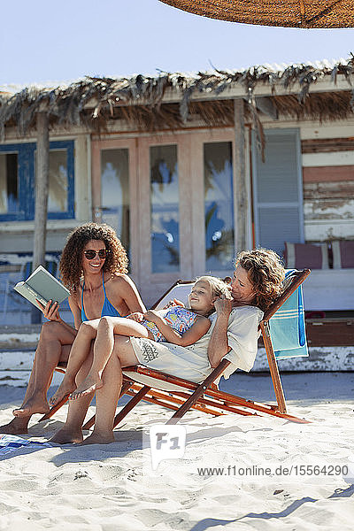 Multi-generation women relaxing  reading book on sunny beach